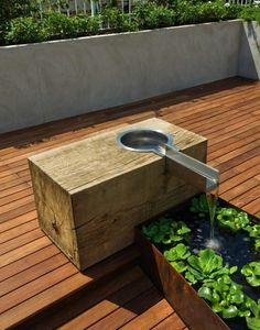 luxus brunnen auf einer terrasse mit grünen pflanzen und hölzernen brettern…