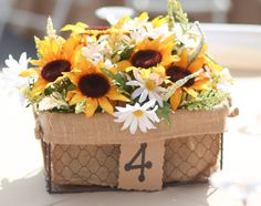 Sunflower wedding centerpieces- I used fake flowers (we got married outside in Florida- real flowers would have wilted in 10 minutes). I found the basket at Joann's for $6, used a piece of foam in the bottom to stick the flower stems into and used card-stock to create the table numbers. Cheap, easy, rustic and cute!