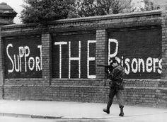 È il 13 maggio del 1981. Un soldato britannico pattuglia Falls Road, a Belfast, in cerca di cecchini. Sui muri una scritta a sostegno di Bobby Sands e degli altri detenuti che scioperano. (Rob Taggart/Central Press/Getty Images)