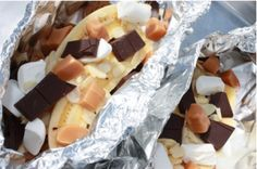 "Crunch sheets of heavy-duty tin foil into a packet shaped like a banana split dish. Place banana in the center and scatter dark chocolate, caramel candies, slivered almonds, graham crakers over the top. Seal the foil, leaving about a 2"" gap over the ingredients. Place next to the fire to bake and get your spork ready!"