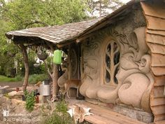 little house with sculpted cob walls looks out over the banks of a small stream in Somerset, England…