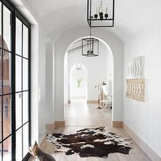 Ryan Street and Associates - entrances/foyers - arched hall, arched hallway, arched ceilings, white walls, hardwood floors, light hardwood floors, lantern pendants, iron lantern, brown and white cowhide, cowhide rug, steel doors, steel and glass doors, steel french doors, archway, arched doorway,