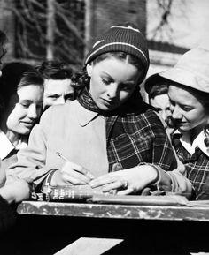 Jeanne Crain signing autographs for a few teenage fans on the set of Margie, 1946