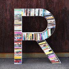 En reol, der lever fuldt op til boligtrenden med bogstaver på væggen: et bogstav til opbevaring af bøger. R'et fås også som E, A, D. Set hos Urban Living