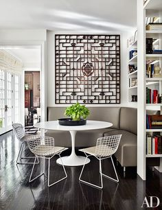 In the breakfast area, an antique Chinese screen from VW Home presides over an Eero Saarinen table and Harry Bertoia chairs, all by Knoll; the chairs' seat cushions are made of an Edelman leather, and the bespoke banquette is covered in a Stark fabric.
