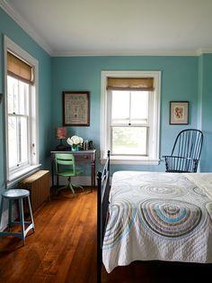 blue room. black metal bed, blinds, simple