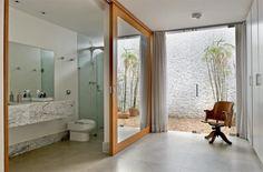 Na suíte principal, a porta de correr espelhada com moldura de cumaru (2,35 x 2,50 m) resguarda o banheiro. Bancada de mármore carrara (Marmoluz) e, na área molhada, pastilhas brancas de resina. Projeto de Gabriela Müller e Gustavo Costa.