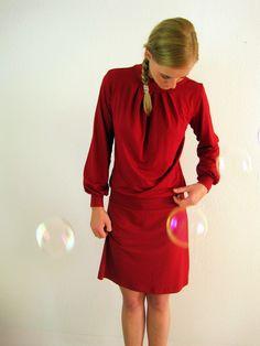 Een lievelingsstuk van prachtige eenvoud en elegantie: een vrouwelijke jurk met verfijnde plooien, die een silhouet van het lichaam laat zien. Aangevu