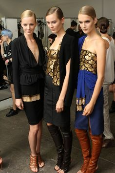 Models backstage and posing with their gold Altuzarra and Swarovski Elements looks.