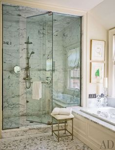 In a Lake Forest, Illinois, cottage, works by Joan Miró brighten a bath, which features a Calacatta marble shower, a Kallista tub, and an Ann Sacks mosaic floor tile. The shower fittings are by Perrin & Rowe, and the stool is by Restoration Hardware.Pin it.
