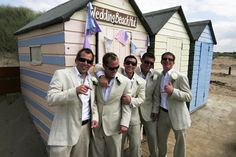 The best man and ushers at the wedding beach hut having fun in the sun