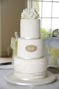 Ivory wedding cake with piped royal icing detail, and custom sugar flowers.