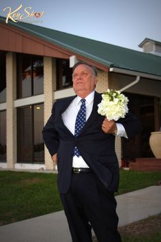 The father of the bride is holding the bouquet and is having fun with it.