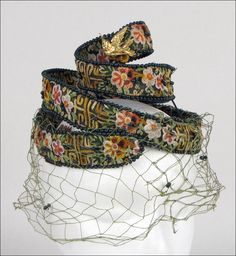 Bes-Ben 'Spiral' Hat | Made in Chicago, United States | Spiral hat is entirely embroidered with floral chain stitching. Beading throughout hat, and green veil, leads to a hummingbird at the top of the spiral