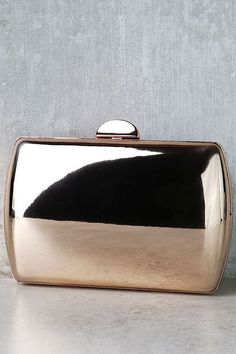 """If there's one accessory you can see yourself wearing over and over, it's the Reflected Image Rose Gold Mirrored Clutch! Reflective, rose gold vegan leather covers this structured clutch with matching metal trim. Top clasp opens to interior accordion sides. Carry as a clutch or attach the 50"""" rose gold chain strap."""
