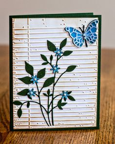 handmade card ... Memory Box dies ... like the pairing of black and royal blue for die cuts ... butterfly ... delicate silhouette flowers and leaves ... aged embossing folder looks like window blinds ...