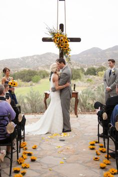 Bride and groom kissing during wedding ceremony with a sun flower theme