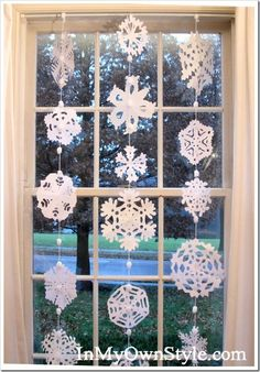 "snowflake window = strands of ""Spark-a-Doodle"" yarn hung from a tension rod, ironed snowflakes + adhesive dot stuck onto strand/pompom"