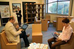 Stanza lettura in cartone, sedie, tavoli e libreria