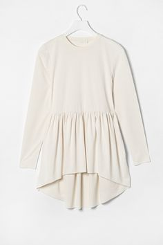 With a delicate crepe texture, this long tunic top has a raw-edged skirt, gathered from the waist and longer at the back. Loosely fitted, it has a simple crew neckline and raw-edged sleeves. 72% Acetate  18% Polyamide  10% Elastane