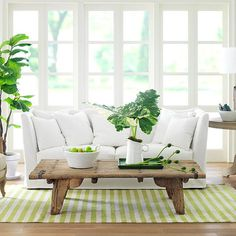 Rustic coffee table paired with a sleek, modern white sofa. Also, love the white+green palette