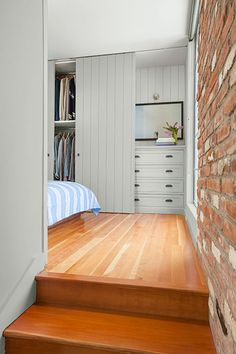 In this master bedroom, built-in bureaus and his-and-hers closets are concealed behind beadboard sliding doors.