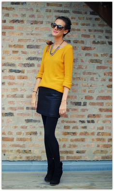 Mustard sweater, rolled sleeves. Leather skirt. Opaque tights. Jeweled necklace. Ankle boots. Shoulder bag.