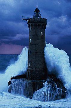 Wave crashing into a lighthouse. Indigo colored sky.