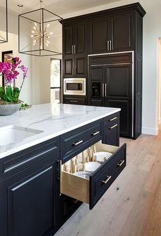Hudson Valley Lighting Glendale Pendants light over a drop down black island with plat pegs, drawers with brass pulls and white quartz countertops.