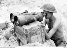 Balikpapan, Borneo. July 1945. Jack Keanne of Stanthorpe, Qld, studies the hills surrounding Balikpapan, through captured giant field glasses which are resting on a wooden crate.