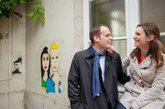 Smiling couple in love with graffiti in Les Marais, by TripShooter Paris photographer Jade Maitre.