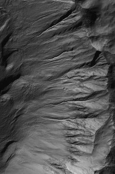 Crisp details in a suite of mid-latitude gullies on a crater wall are captured in this Mars Global Surveyor (MGS) Mars Orbiter Camera (MOC) view obtained in southern winter on 12 October 2006. During southern winter, shadows are more pronounced and the atmosphere is typically quite clear. These gullies, which may have formed in relatively recent martian history by erosion caused by flowing, liquid water, are located in a crater on the east rim of Newton Crater. Credit: NASA/JPL/Malin Space