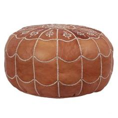 Handmade leather pouf with a dark tan arch motif.Product: PoufConstruction Material: Moroccan leatherColor: Dark tanFeatures:    HandmadeArch design  Dimensions: 14 H x 21 Diameter