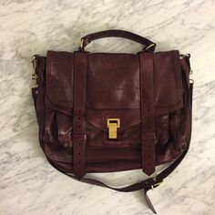 "Proenza Schouler PS1 Large Satchel - Burgundy Leather flap front satchel bag with brass hardware; metal closure and leather pull tab straps with exterior back zipper pocket. Can be worn with top handle or shoulder strap (detachable and adjustable). Zipper pocket and large slip pocket in the front body under the flap. Fabric lined interior with leather trimmed zipper pocket and snap tab closure. Measurements: 11"" H and 14"" W. Made in Italy. Condition: Worn and water marks throughout, however…"