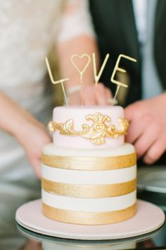 Gold wedding cake with 'Love' topper. Ruffled – photo by http://mustardseedphoto.com/ – http://ruffledblog.com/romantic-paris-elopement/