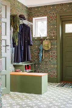 En hall med tapet, hatthylla och pärlfranslampa. Tapeten är nytillverkad efter ett originalmönster från 20-talet.