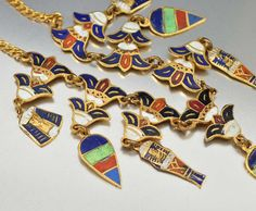 Superball original Art Deco Egyptian themed necklace, handcrafted with dangling enamel charms backed with gold gilt. Double lotus flowers have colorful enamel