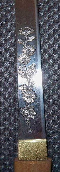 Antique Japanese wakizashi sword blade showing the horimono of a chrysanthemum.