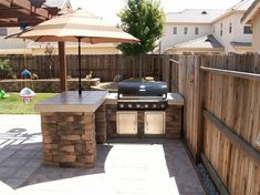 Outdoor entertaining area - love the stone base, built in grill, and umbrella. Would be great for all our cookouts with friends! www.homes.com/...