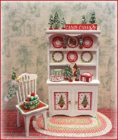 "Merry and Bright Holiday Vignette - THIS KIT INCLUDES: the hutch, the chair, stacking boxes, little trees, ornament basket & ornaments, the rug and all the artwork. Finished Size: Hutch approx 1"" w x 1 3/4"" h. Chair approx 1/2"" w x 1"" h"