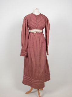 Dress of brownish-pink twilled silk (sarcenet or foulard) the bodice with round neck and centre front opening (pinned to fasten) and with applied piped bands fabric to neck and in four diagonal strips across front bodice; long sleeves slightly gathered fullness at shoulder, deep cuffs with piped vandyking and tabs; medium high waistline; skirt with fall-flap front with tie tapes and gathered at back waist; full length skirt with four-band padded hem; bodice lined in cotton. 1815 - 1820…