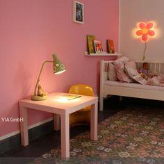 Die Fliesen mit einem abstrakten Blumenmuster in den Farben Rosa, Grün und Weiß wirken mädchenhaft und romantisch. Die rosafarbene Wand greift eine der Farben…