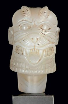 A NEO-ASSYRIAN CHALCEDONY HEAD OF PAZUZU CIRCA 8TH-7TH CENTURY B.C. The demon god grimacing, revealing fangs and a lolling tongue, with leonine features including a thick beard crosshatched along the jaw line, and a feline-whiskered snout, the ridged brows protruding above the bulging eyes, with human ears and a bald pate, the tapering ribbed horns curving back over the forehead, perforated vertically