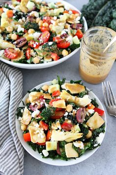 Mediterranean Kale Salad with chickpeas, tomatoes, cucumber, red pepper, artichoke hearts, olives, feta cheese, pita chips and a simple hummus dressing. This salad is perfect for lunch, dinner, potlucks, and parties!