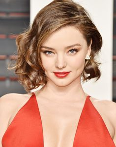 Miranda Kerr wears shimmery eyeshadow and winged liner with a a glossy bold red lip