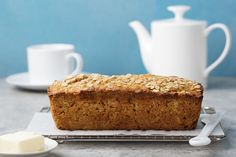 Healthy vegan oat, coconut loaf bread, cake on a cooling rack Grey and blue stone background Copy space