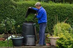 Man filling compost bin in garden - Dr T J Martin/Moment Open/Getty Images