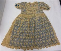 This girls party dress was worn in 1892-1893 is made of machine lace and is lined with silk. It is a typical of girls fashion at the time. The dress was once a top and skirt but was altered and made into a dress.