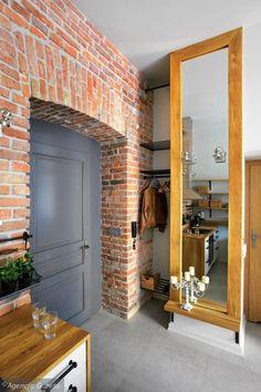 Drzwi do mieszkania otacza ceglana ściana z pięknym łukiem, którą gospodarz odsłonił własnymi rękami.