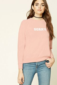 """A fleece knit sweatshirt featuring a """"Sorry"""" graphic on the chest, """"Not Sorry"""" graphic down one sleeve, a crew neck, long raglan sleeves, and ribbed trim."""